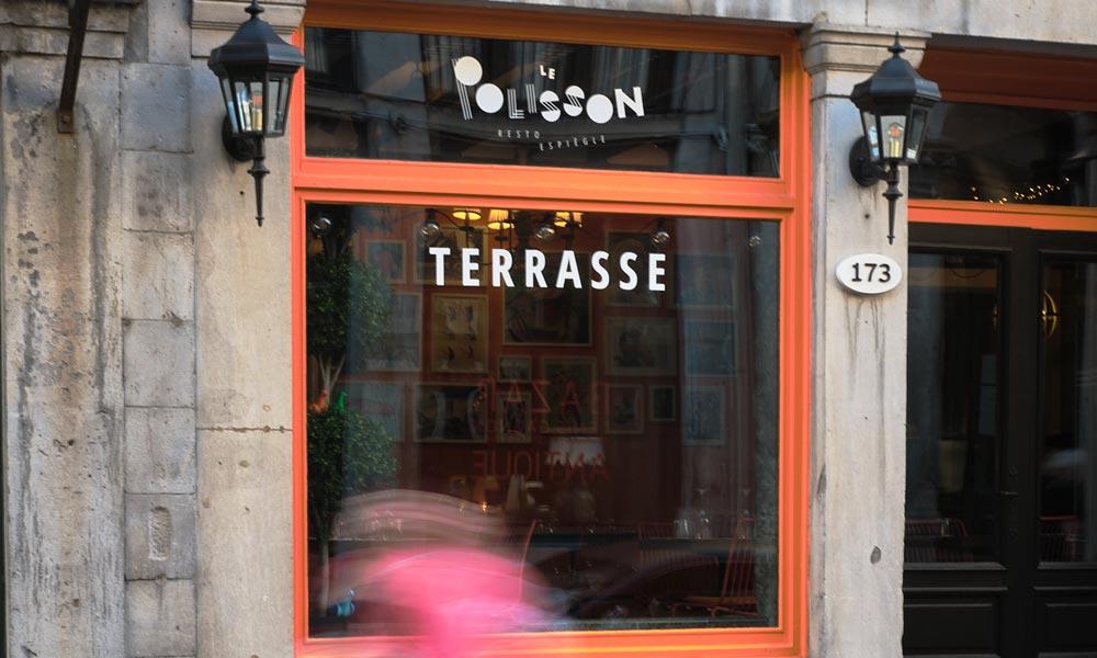 Fenêtre avec le logo Resto le Polisson et TERRASSE dans le Vieux-Montréal